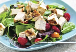 A picture of a healthy salad with chicken, raspberries, tomato and spinach. .