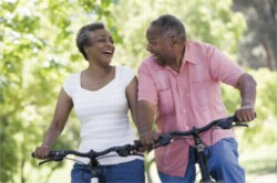A smiling, older couple bikes on a wooded trail.