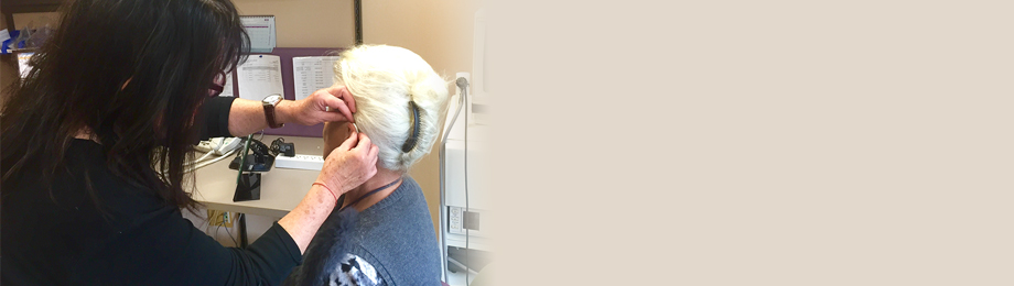Audiologist placing hearing aid on patient