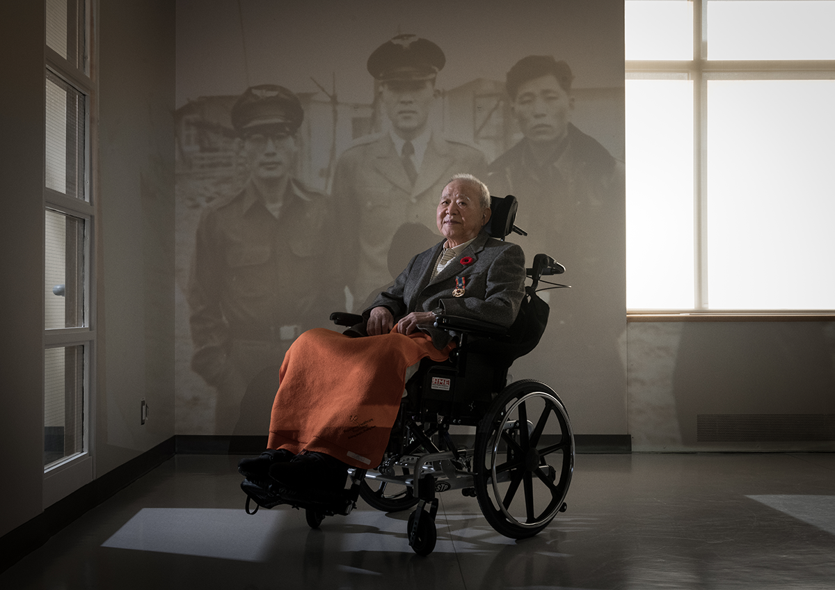 Beong Soo Kim pictured in front of an image of himself during the war