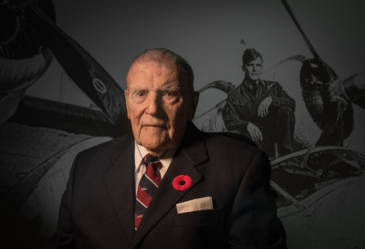 Nelson King is photographed in front of an image taken of himself during war times.