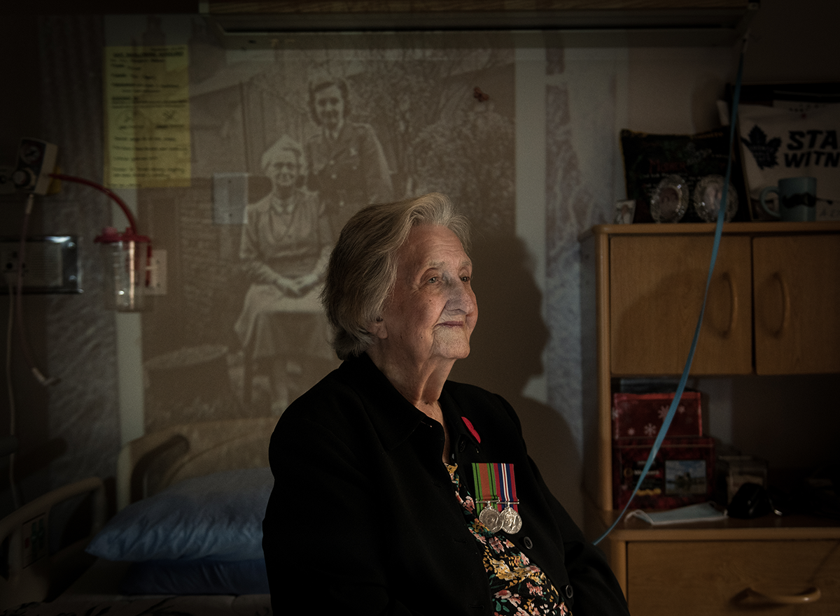 Margaret Addison, pictured wearing her medals. She sits in front of a projected image of herself during the war.