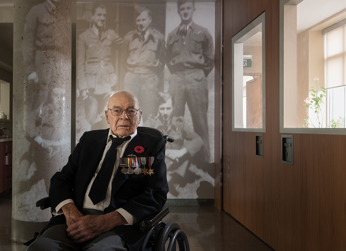 Ken Hawthorn sits pictured in front of an image of himself and others during the war