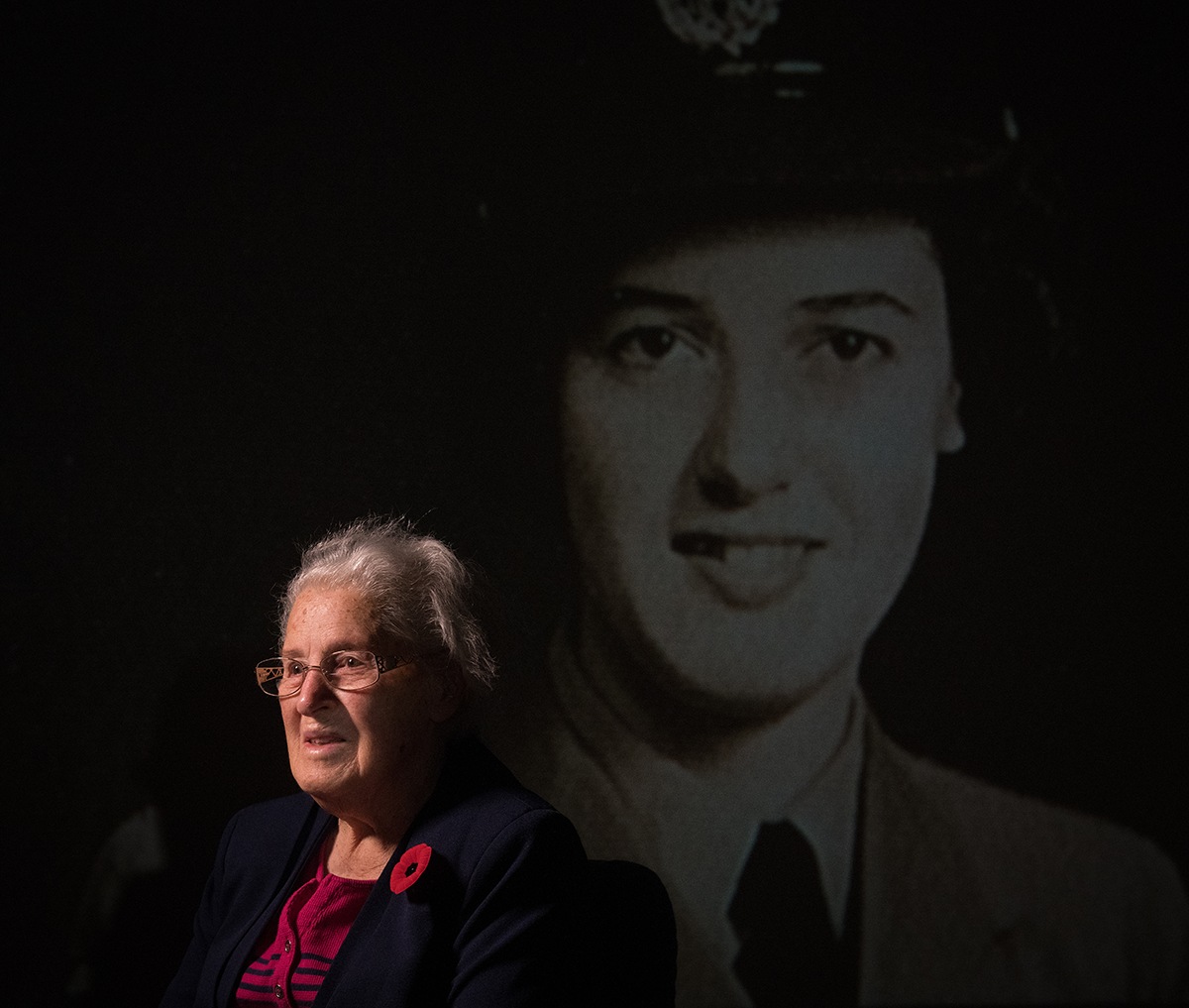 Isobel Montgomery, sits in front of a projected image of herself during the war times