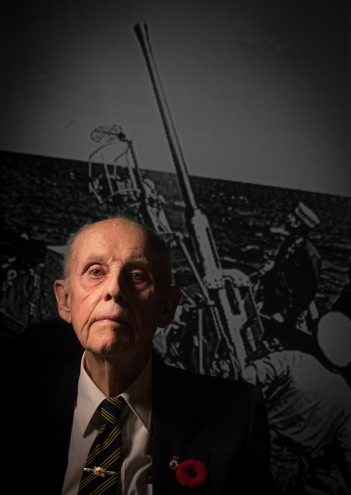 Jim Lister is photographed in front of an image of himself taken during the war times.