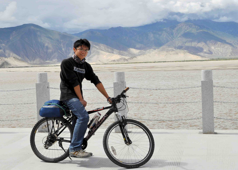 Haoran in front of an impressive mountainscape, on a bicycle