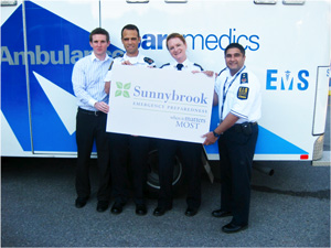 An image of a paramedics team in front of an ambulance holding up a Sunnybrook logo sign