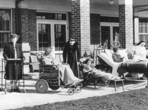 Historical image of patients convalescing in beds, wheelchairs & crutches